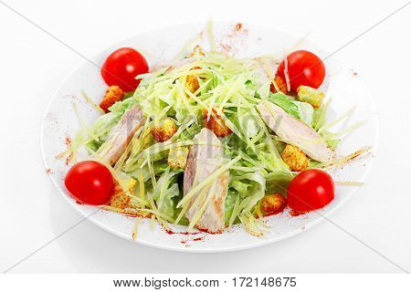 Caesar salad with chicken, iceberg lettuce, parmesan cheese, Caesar dressing, chicken, cherry tomatoes on a white plate on a white background