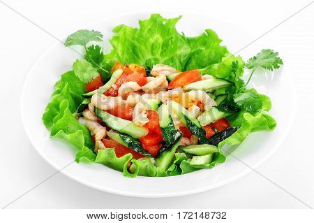 Vegetable salad with shrimp, cucumber, tomatoes, garlic, shrimp on a white plate on a white background