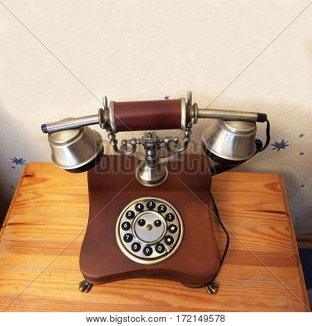 Vintage wired phone with round disc for dialing. Apparatus to transmit human speech at distance the telephone wire, made of wood and metal. Ancient technology - harbingers of modern development.