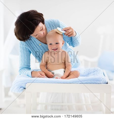 Mother and baby change diaper after bath in white nursery with bed and rocking chair. Little boy on changing table in clean dry nappy. Mom taking care of infant child. Kids room interior and hygiene.