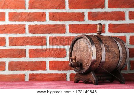 Wooden barrel with iron rings on brick wall background