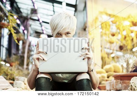 Hipster girl with blonde hair hidden Behind opened laptop computer sitting on stairs in a park outdoor sunshine and plants at the background.