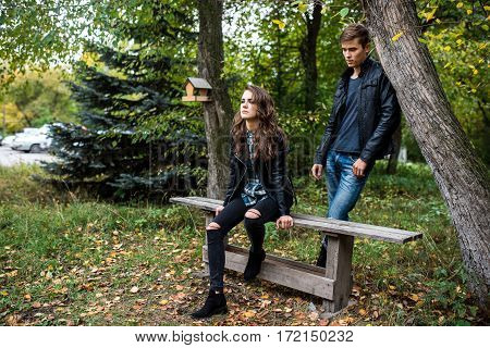 Beautiful young couple in the street in the summer. A girl sits on a bench behind her man leans on a tree trunk