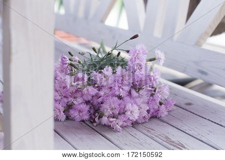 bouquet of pink flowers on a white wooden background outdoors