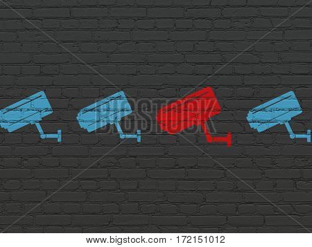 Privacy concept: row of Painted blue cctv camera icons around red cctv camera icon on Black Brick wall background