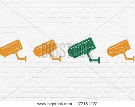 Safety concept: row of Painted orange cctv camera icons around green cctv camera icon on White Brick wall background