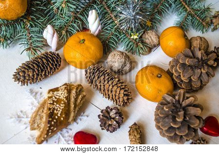 Coniferous branch with tangerines, pine cones with sweets on light table