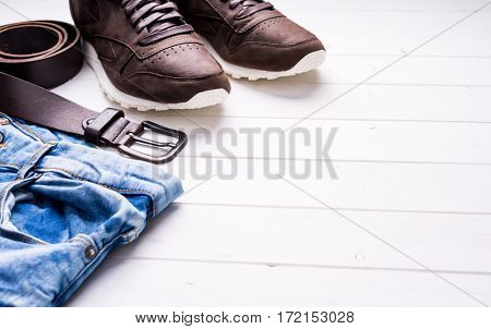 male jeans, belt and shoes on wooden background with text space, top view