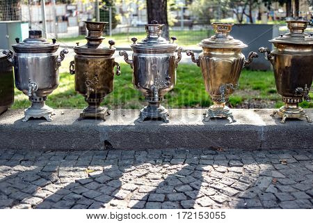 Old brass samovars sitting on the street waiting to be sold