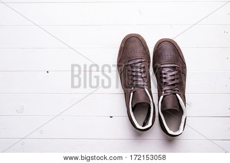 brown leather shoes with laces on wooden background with empty text space