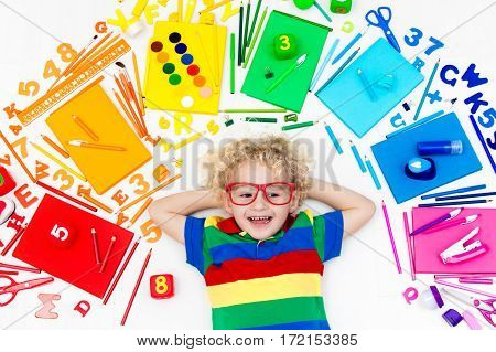 Little boy with school supplies books drawing and painting tools and materials. Happy back to school student. Art and crafts for kids. Child learning rainbow colors alphabet letters and numbers.