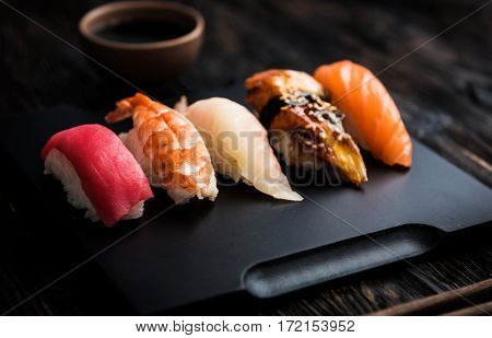 sashimi sushi set with  soy on black background