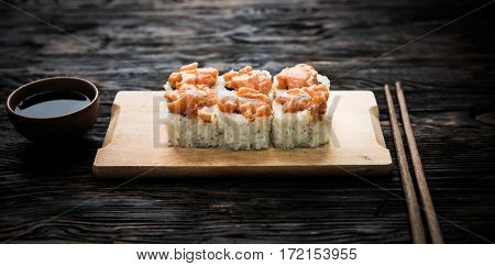 closeup of a set of sushi rolls with salmon topping on wooden board