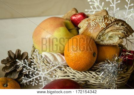 Straw basket with pastries,yellow apple,tangerines,pine cones and snowflakes