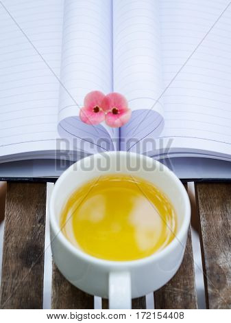 Couple of Crown-of-thorns flower and a cup of tea with heart shape on wooden table which made by white paper notebook