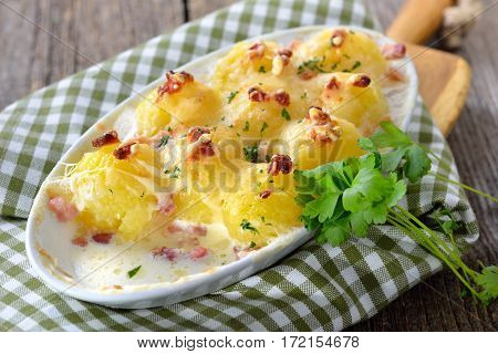 Hearty potato dumplings baked with cheese and bacon, freshly served from the oven