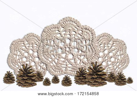 Fir cones on the background of knitted napkins and snowflakes