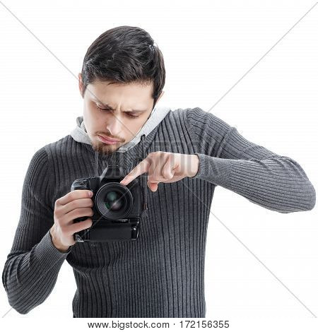 young photographer in shirt sets up the camera isolated on white background. guy learns to photograph