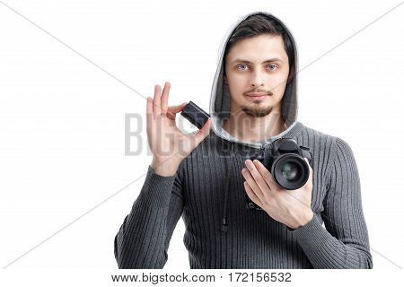 young  professional photographer in shirt  holds the battery for DSLR digital camera isolated on white background