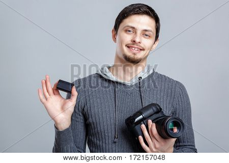 young smilling professional photographer in shirt  holds the battery for DSLR digital camera on grey background