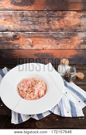 Tasty Risotto With Seafood And Red Caviar Of Flying Fish With Rosemary On Wooden Background