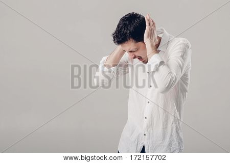 Frustrated young brunette man in a white shirt with headache on  gray background. terrible migraine. soft light