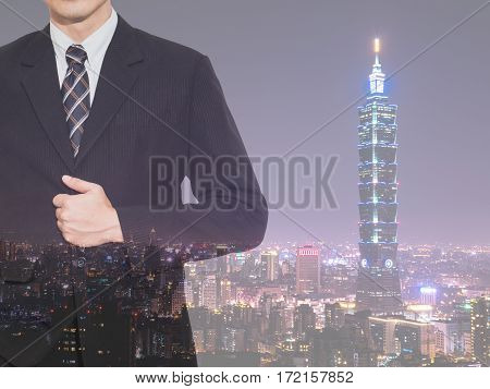 Double exposure of smart business man wear black suit stand on modern building in night light cityscape