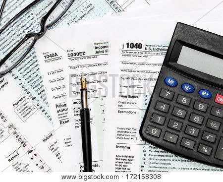 Pen glasses and calculator on tax form 1040. business concept. Top view.