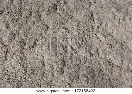 Grey brown arid cracked lumpy dry textured desert soil
