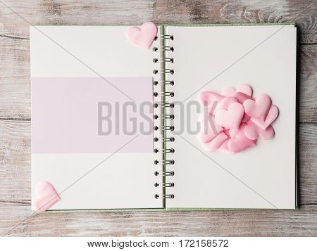 Pink hearts on open notebook with purple blank card. Valentine's mother day or baby birthday greeting card wedding invitation