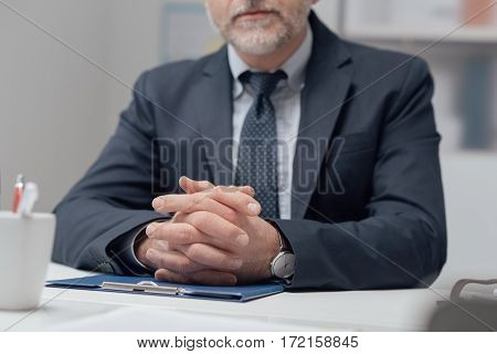 Confident businessman sitting at office desk and waiting with hands clasped corporate business concept