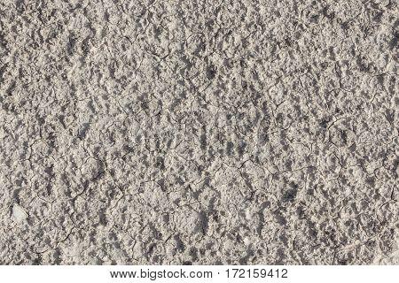 White arid cracked lumpy dry textured desert soil from above