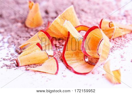 Cosmetic pencil shavings with powder on background.