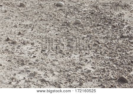 White arid cracked lumpy dry textured desert soil with brown black stones on slope from side
