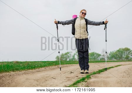 woman with trekking pole in hand , walking with backpack outdoors, Nordic walking
