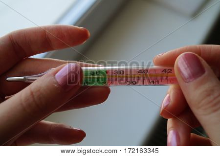 hand girl, doctor holding a mercury thermometer