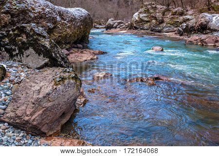 Beautiful winter landscape with turquoise mountain river and granite canyon