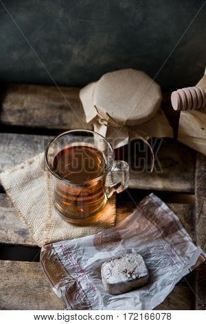 Glass cup with hot tea with jar of honey or jam wood spoon Spanish cookie polvoron on vintage box grey wall background rustic vintage interior cozy atmosphere top angle view