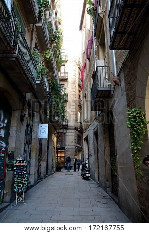 Barcelona Spain - December 3 2016: Narrow street in Barcelona city Spain. Unidentified people visible.