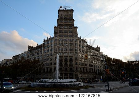 Barcelona Spain - December 3 2016: High building at roundabout in Barcelona city Spain. Unidentified people visible.