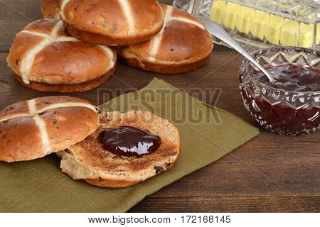 hot cross bun with strawberry jam on green napkin