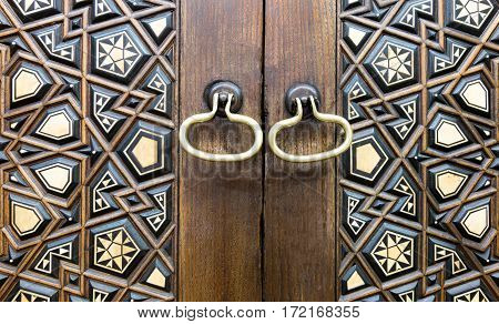 Closeup of two golden ring door knobs over an aged decorated wooden door Medieval Cairo Egypt