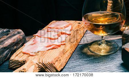 Sliced ham on rustic wood board amid other boards. Glass of brandy on black wood surface
