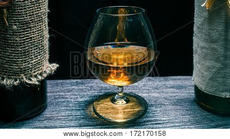 Brandy snifter between two retro wine bottles on black wood