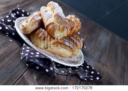 Tasty eclairs on wooden table close up