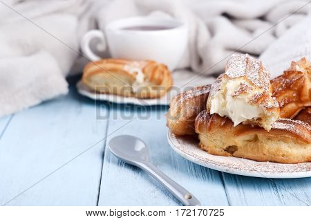Tasty Eclairs On Wooden Table