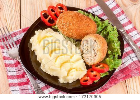 two fried breaded cutlet with mashed potatoes and lettuce on a black plate and a wooden background.