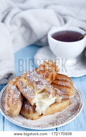 Tasty eclairs with a cup and a blanket on wooden table . Winter style