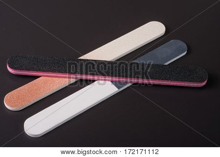 Three nail file with a different abrasive on a dark background.