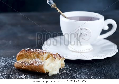 eclair with powdered sugar and cup of tea on the concrete a dark background